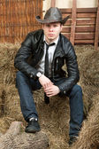 Handsome cowboy in leather jacket in the rural interior. — Stock Photo