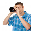Handsome young man holding camera lens like it was spyglass on w — Stock Photo #11544172