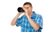 Handsome young man holding camera lens like it was spyglass on w — Stock Photo
