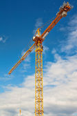 Tall white tower crane against bright blue sky. — Stock Photo