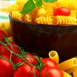 Delicious twig of tomatoes with several pasta types — Stock Photo