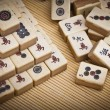 Old chinese game mahjongg on bamboo mat background — Stock Photo #11038641