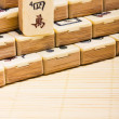 Old chinese game mahjongg on bamboo mat background — 图库照片
