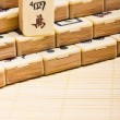 Old chinese game mahjongg on bamboo mat background — Stock Photo #11038970