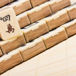 图库照片: Old chinese game mahjongg on bamboo mat background