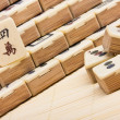Photo: Old chinese game mahjongg on bamboo mat background