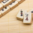 Old chinese game mahjongg on bamboo mat background - Stock Photo