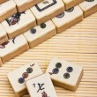 Stock Photo: Old chinese game mahjongg on bamboo mat background