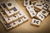 Old chinese game mahjongg on bamboo mat background — Stock Photo