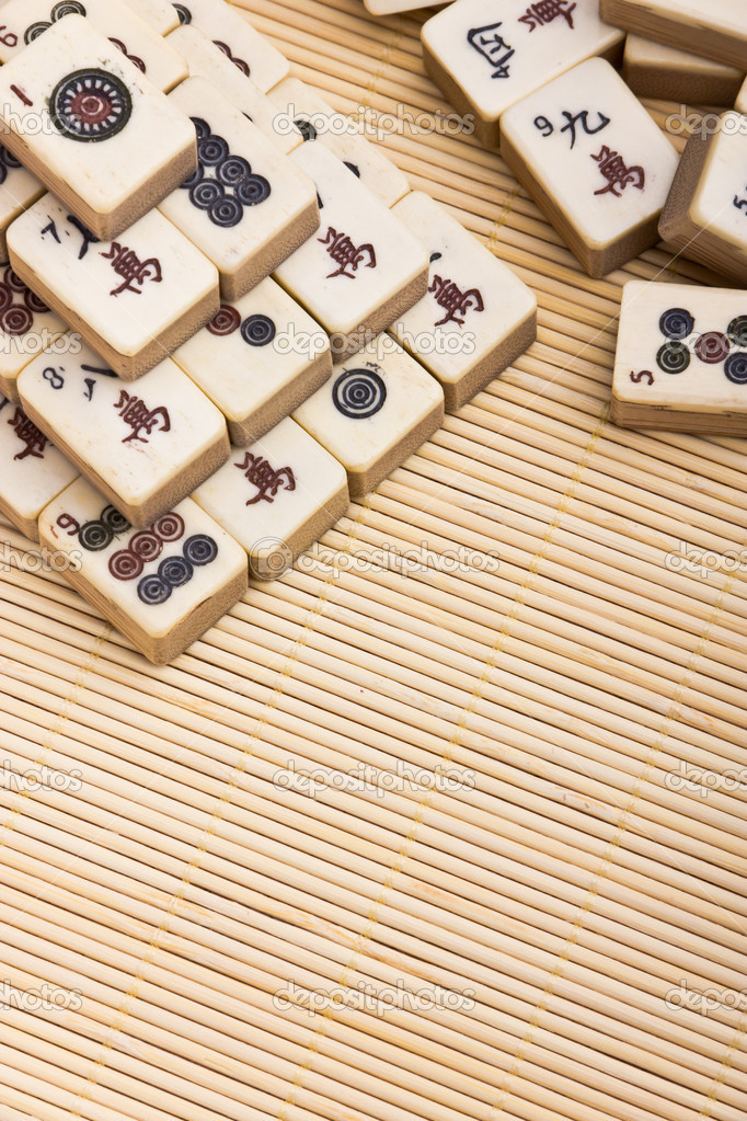 Old chinese game mahjongg on bamboo mat background — Stock Photo #11038758