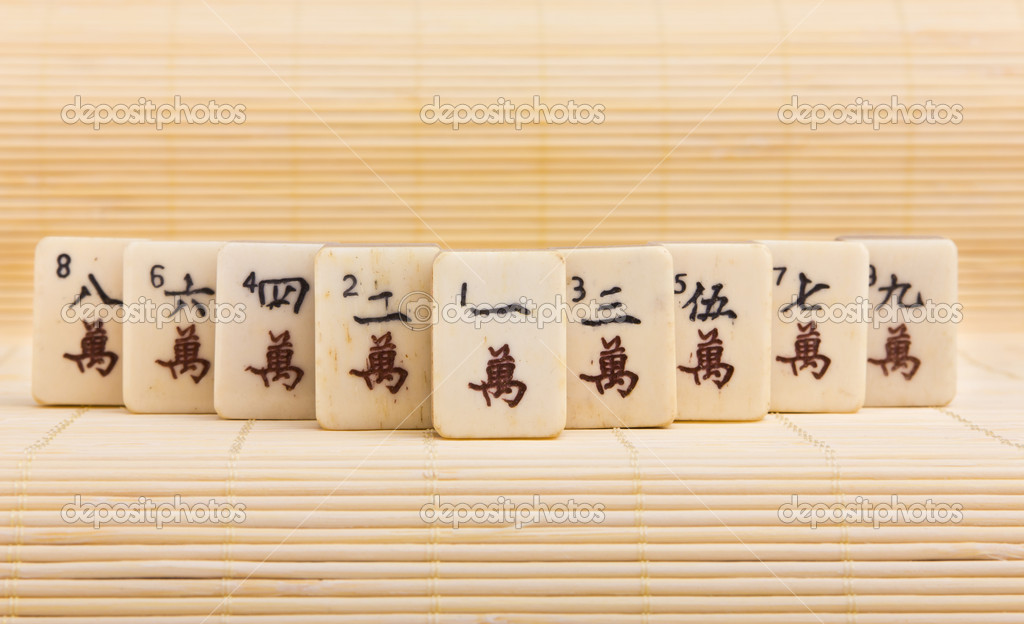 Old chinese game mahjongg on bamboo mat background — Stock Photo #11038835