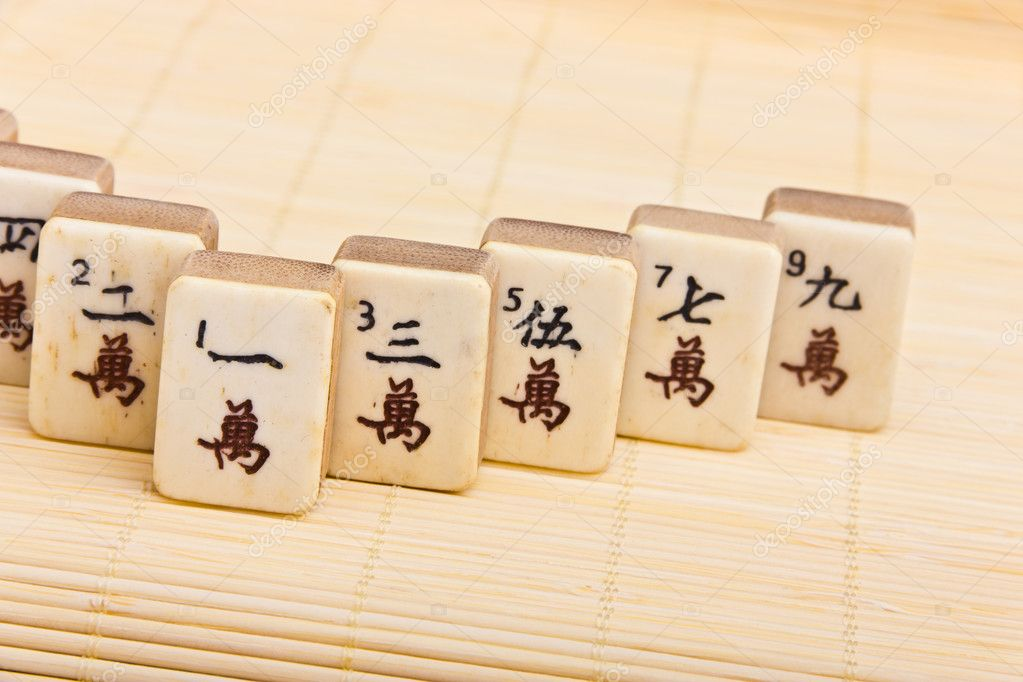 Old chinese game mahjongg on bamboo mat background — Stock Photo #11038895