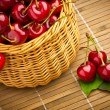 Delicious sweet cherry fruits in wicker basket — Stock Photo