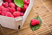 Delicious sweet raspberries on wooden background — Stock Photo