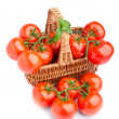 Wicker basket full of delicious tomatoes - Stock Photo