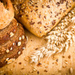 Collection of baked bread on wooden background - Stock Photo