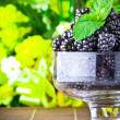 Sweet fresh fruits in glass goblet with mint leaf - Stock Photo