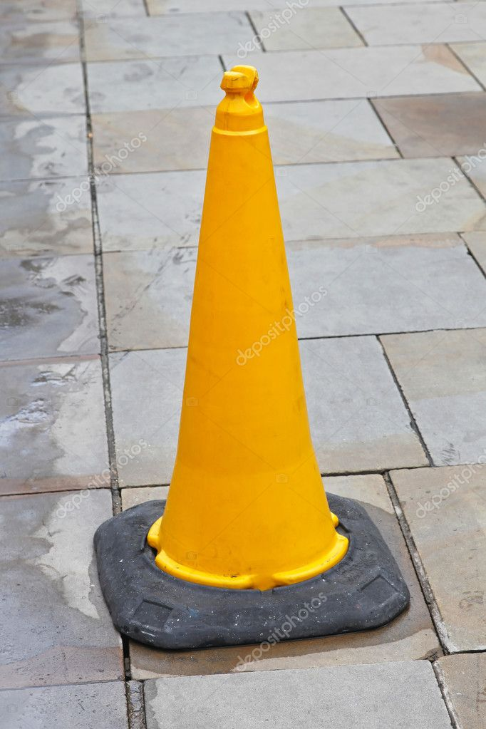 Yellow traffic cone at pedestrian pavement walkway  Stock Photo #11644359