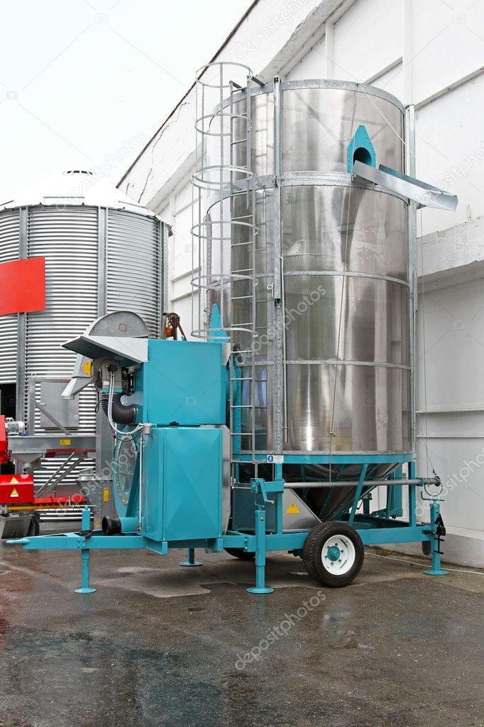 Mobile style cereal dryer at trailer in front of farm  Stock Photo #11732435
