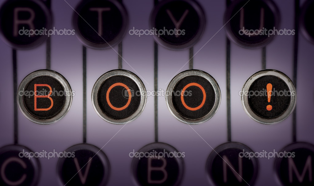 Image of old typewriter keyboard with scratched chrome keys that spell out BOO! in orange letters. Lighting and focus are centered on BOO!  Stockfoto #11469804