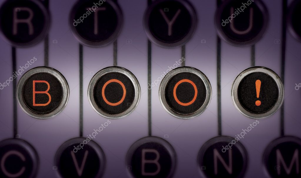 Image of old typewriter keyboard with scratched chrome keys that spell out BOO! in orange letters. Lighting and focus are centered on BOO!  Stock fotografie #11469804