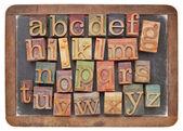 Letterpress alphabet on balckboard — Stock Photo