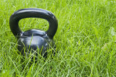 Heavy iron kettlebell in grass — Stock Photo