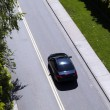 Постер, плакат: Car Driving Down Road From Above Green Grass