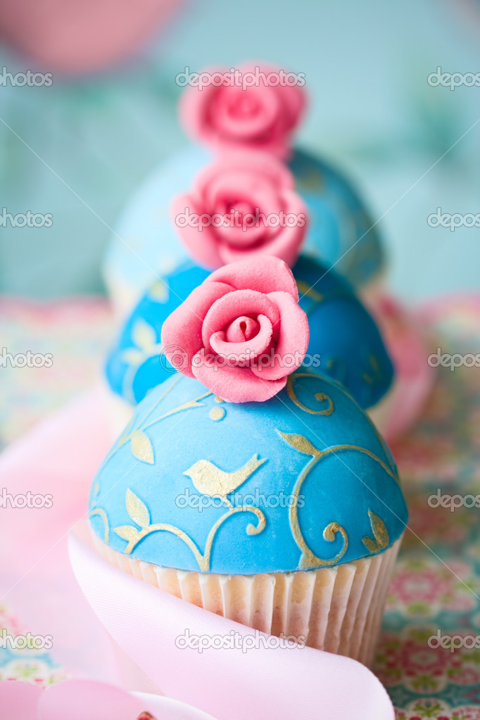 Cupcakes decorated with turquoise fondant and pink sugar roses — Stock Photo #11973545