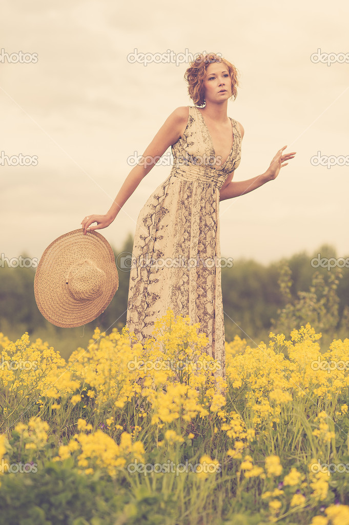 A beautiful young brunette in a summer field  Stock Photo #11114567