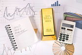 Gold bars on graphs and statistics — Stock Photo