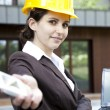 Young female construction engineer with phone - Stock Photo