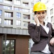 Young female construction engineer with phone — Stock Photo