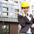 Stock Photo: Young female construction engineer with phone