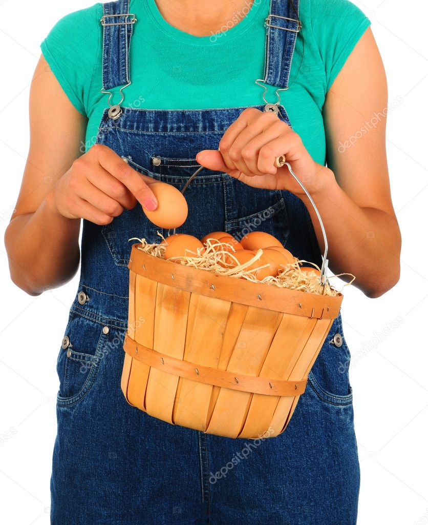 Closeup of a Farm Girl putting a fresh picked egg into a basket held in front of her body. Girl is wearing overalls and a t-shirt and is unrecognizable.  Foto Stock #10932966