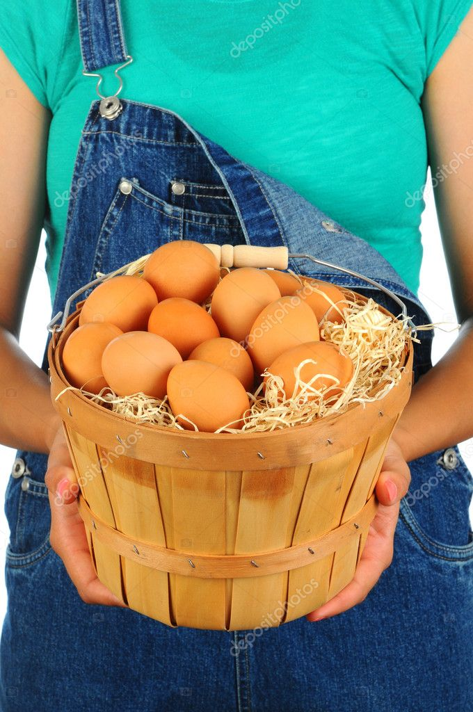 Closeup of a Farm Girl holding a basket of fresh eggs in front of her body. Girl is wearing denim overalls and a t-shirt and is unrecognizable. — Stock Photo #10932974