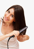 Smiling young woman straightening her hair — Stock Photo