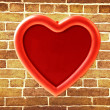 Red photo frame on old brick wall — Stock Photo