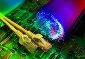 Tablero de circuito impreso electrónico con red cable closeup sobre fondo óptico de fibra — Foto de Stock