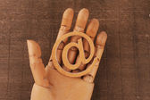 Wooden mannequins hands, holding email symbols — Stock Photo