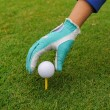 Gloved hand putting a golf ball on a tee — Foto Stock