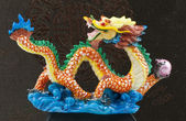 Blue and gold chinese dragon statue at black wall — Stock Photo