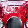 图库照片: Close up view of front of cherry red 1963 Morg+4 vintage automobile