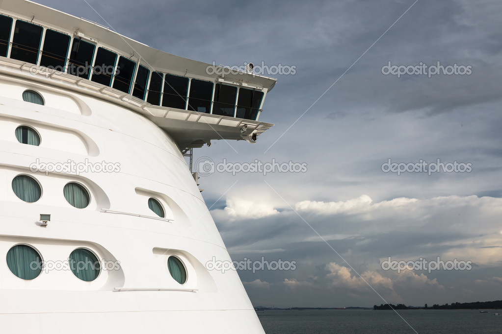 A half frontal view of a cruise ship with a brewing storm in the background — Stock Photo #11237248