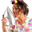 The girl in hair curlers with an iron - Stock Photo