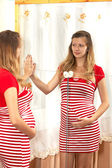 The pregnant woman looks in a mirror — Stock Photo