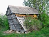 Verlaten oude houten klein gebogen huis — Stockfoto