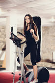 Beautiful woman at the gym on stationary bicycle — Stock Photo