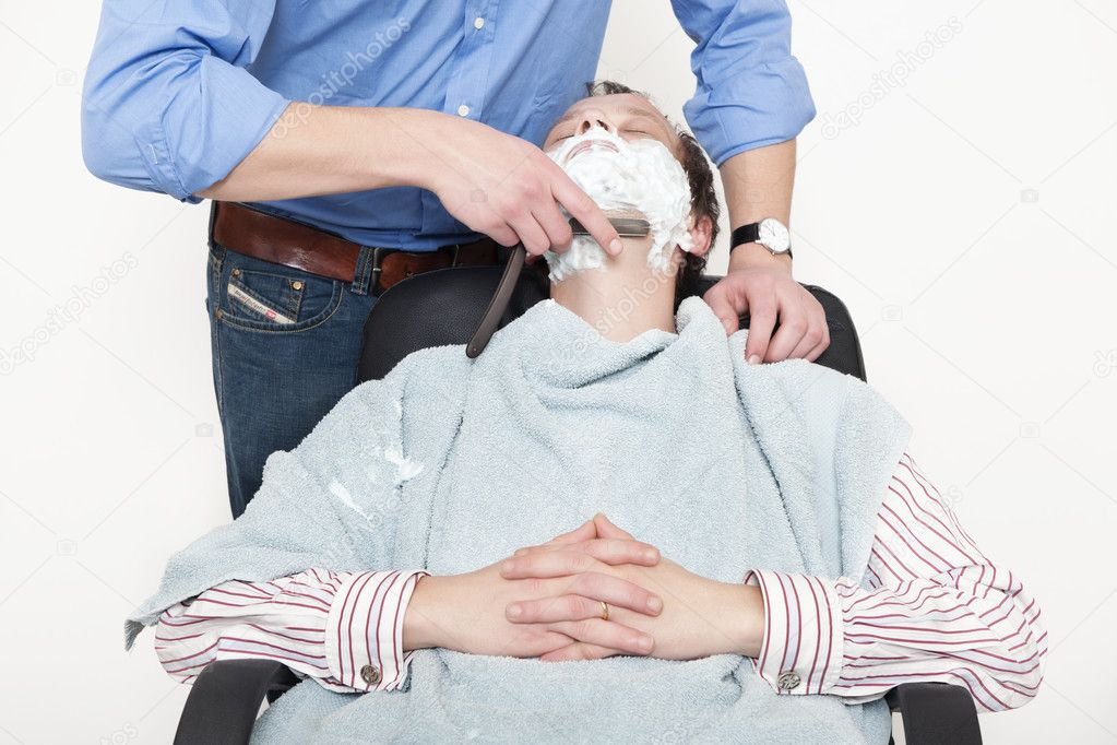 Man wrapped in towel being shaved with cut throat razor by barber over colored background — Foto Stock #10949575