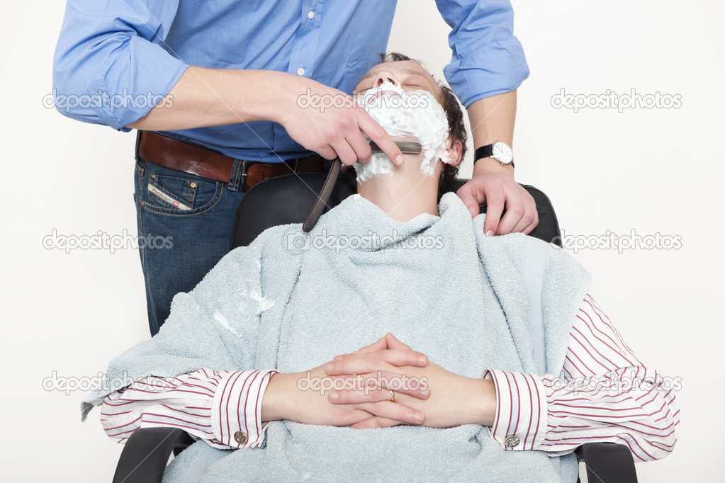 Man wrapped in towel being shaved with cut throat razor by barber over colored background — Stockfoto #10949575